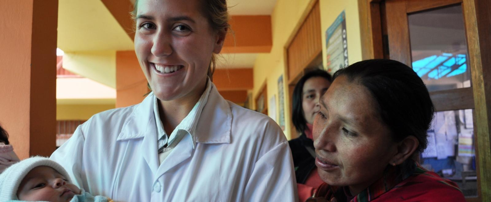 A student doing her Midwifery internship abroad holds a new-born infant at a local hospital.